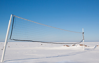 Snow covered beach volleyball court with net. Blue sky and deserted frozen bay background.