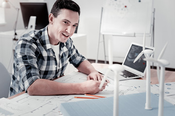 Dreams come true. Professional architect keeping smile on his face and leaning arms on table while looking aside