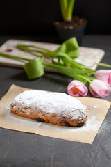 freshly baked cake with sweets, raisins and candied fruits, sprinkled with powdered sugar on a gray table with pink tulips