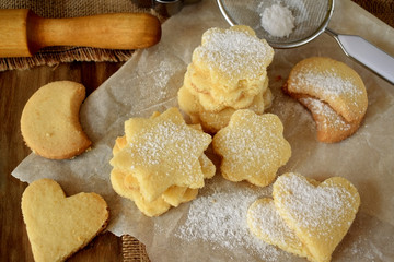 Shaped shortbread cookies covered with sugar powder surrounded by kitchen utensils