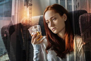 Depressed woman. Young depressed woman sitting in an armchair and looking at the glass with alcohol while being home alone and feeling depressed