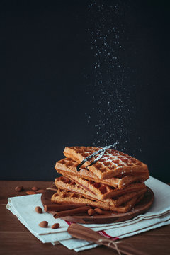 Sweet potato waffles stacked on wooden plate