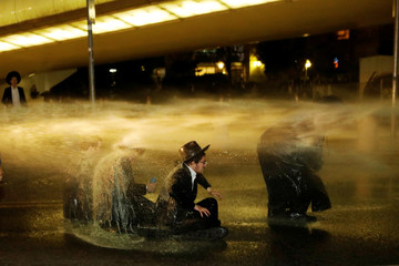 Israeli ultra-Orthodox Jewish men sit as a water cannon is activated during a protest against the detention of a member of their community who refuses to serve in the Israeli army, in Jerusalem