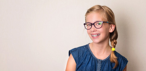 Health, education and people concept. Closeup portrait of happy teen girl in braces and eyeglasses.