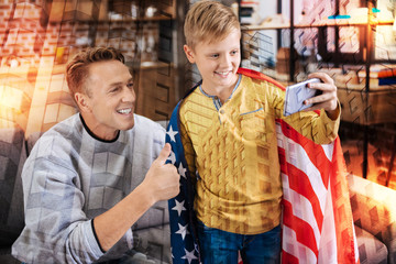 Positive photo. Positive smiling little boy standing with a big American flag on his shoulders and looking glad while taking emotional photos with his kind attentive loving father