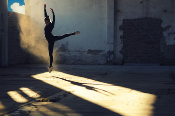 Silhouette of ballerina jumping in abandoned building