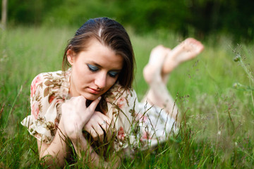 A beautiful brunette in a dress and a long scythe with a desired facial expression, lying on her stomach in the grass relaxes. The girl enjoys nature.