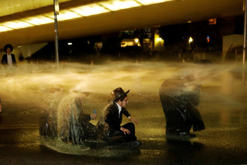 Israeli ultra-Orthodox Jewish men sit as a water canon is activated during a protest against the detention of a member of their community who refuses to serve in the Israeli army, in Jerusalem