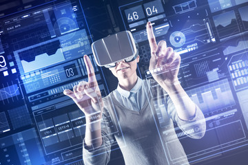Finding solution. Smart experienced professional programmer wearing virtual reality glasses and pointing to the transparent screen while getting an interesting idea