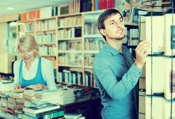 Young cheerful male customer searching new book