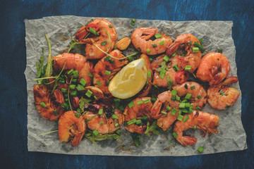 Large grilled BBQ shrimp with sweet chili sauce, green onion and lemon. Vintage toned image