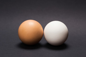White and yellow egg on a black background. Close-up.