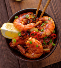 Large grilled BBQ shrimp with sweet chili sauce, green onion and lemon. Top view