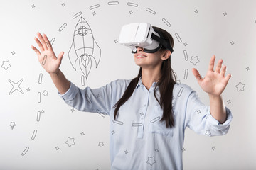 Virtual reality. Young progressive woman feeling impressed and smiling while wearing modern convenient virtual reality glasses and exploring the space with a help of them