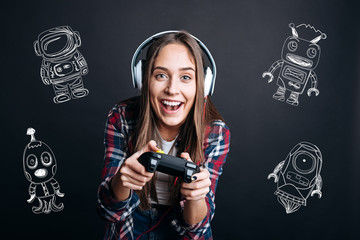 Funny game. Positive excited young woman feeling happy while sitting with a modern game console and playing a wonderful computer game