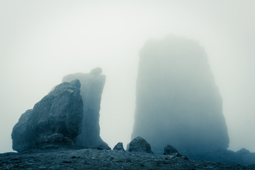 Roque Nublo big rock mountain covered with heavy fog in Gran Canaria, Spain. Futuristic sci fi landscape setting. Thriller, mysterious empty space. Blue effect