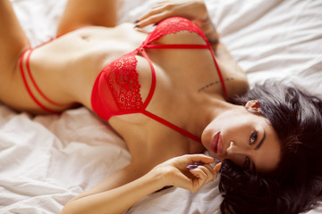 Woman in red lingerie is laying on the bed in bedroom.