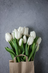 Bouquet of white tulips in a kraft paper bag on a gray concrete background. Top view. Flat lay. Postcard for Easter, Mother's Day and Spring Holidays.
