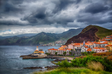 A small town whith the lighthouse by the ocean and the mountains. Portugal, Madeira Island, Canical
