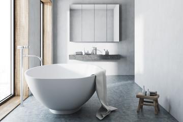 White bathroom, white tub, concrete floor