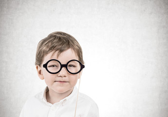 Cute little boy with glasses, concrete