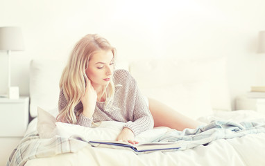 Fototapete - young woman reading book in bed at home