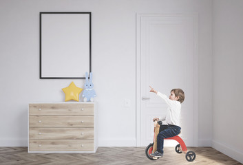 Cute boy on a tricycle in his nursery, poster