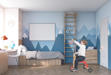 Cute boy on a tricycle in his room