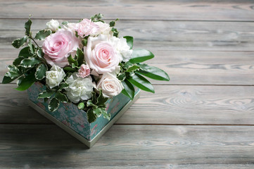 Bouquet from roses and white clove in a gift box on a wooden table