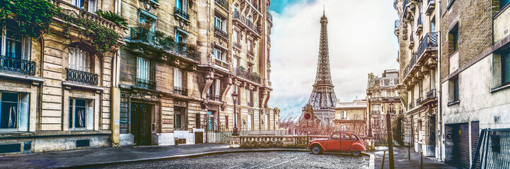 Photo sur Toile Tour Eiffel The eiffel tower in Paris from a tiny street with vintage red 2cv car
