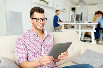 man in glasses with tablet pc working at office