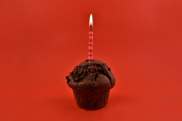 Chocolate muffin with candle stock images. Muffins on a red background. Birthday muffin with cake candle