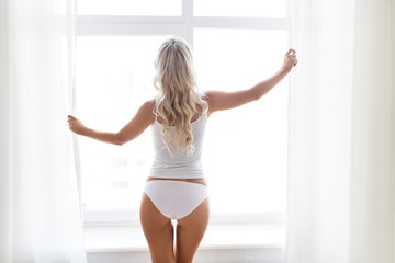 woman in underwear at window in morning
