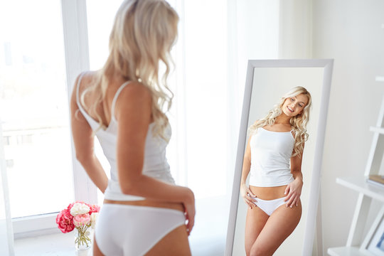 woman in underwear looking at mirror in morning