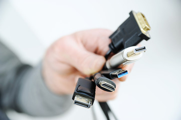The  various cords and plugs in the hand.