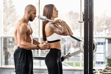 Young woman with her personal trainer working out in gym