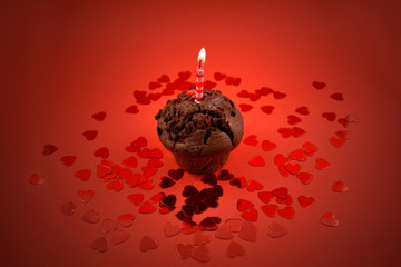 Muffin with candle stock images. Chocolate muffin with heart on a red background. Sweet birthday pastry. Valentines Day concept
