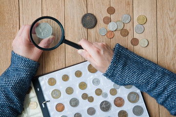 Woman-numismatist views coins from a coin album through a magnifying glass. Top view