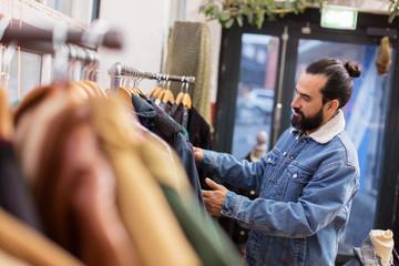 man choosing clothes at vintage clothing store
