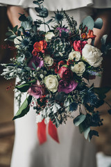 bridal bouquet of bride from red and white roses and green branches