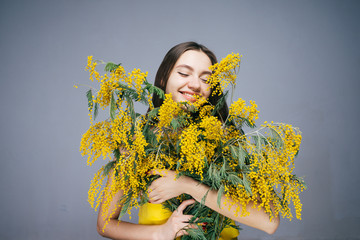 happy woman holding a large bouquet of yellow flowers in hands, on March 8
