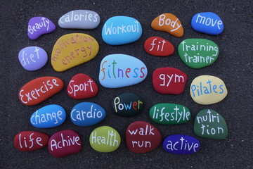 Fitness and diet for a better life, conceptual colored stones over black volcanic sand