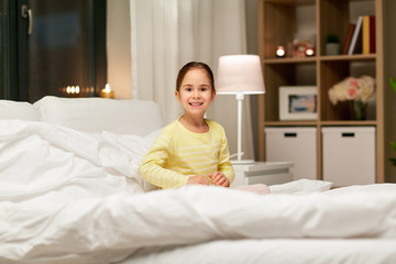 happy little girl in bed at home at night