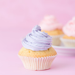 Cupcake decorated with pink and violet buttercream on pastel pink background. Sweet beautiful cake. Square banner, greeting card for birthday, wedding. Close up photography. Selective focus