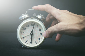 Hand with old watch showing time