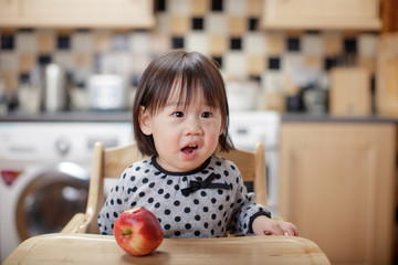 baby girl eat apple at home kitchen