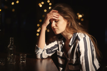 Young drunk woman at table in bar. Alcoholism problem