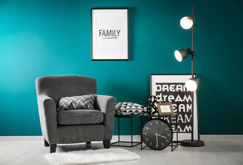 Stylish lamp and comfortable armchair in room interior near color wall