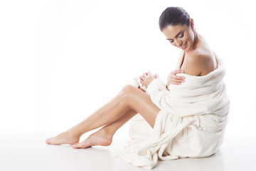 Beautiful and natural woman in white bathrobe is touching her skin. Relax and comfortable feelings only.