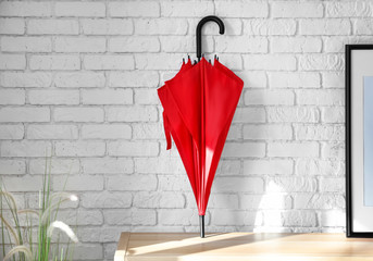 Stylish red umbrella on table near brick wall